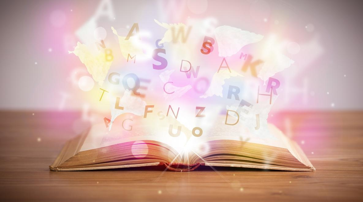 Open book with colorful letters bursting out