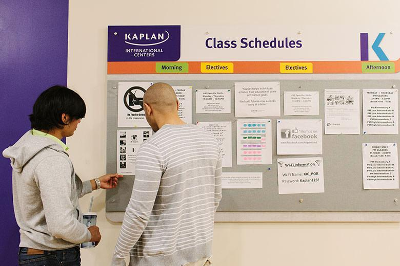 Kaplan students looking the class schedule in Portland school
