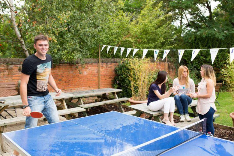 Kaplan students playing ping pong and relaxing in the school garden
