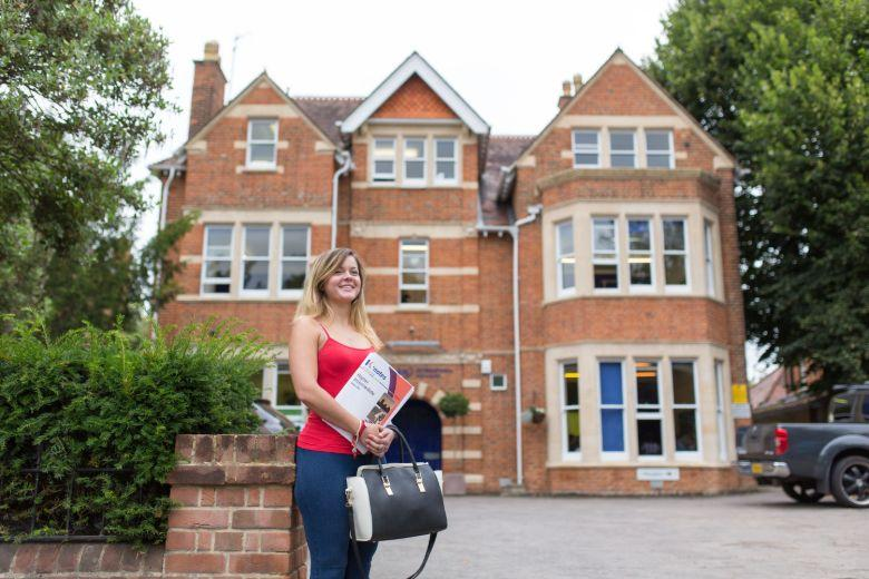 Student standing in front of the building of Kaplan Oxford School